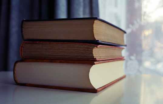 three piled books on white wooden table