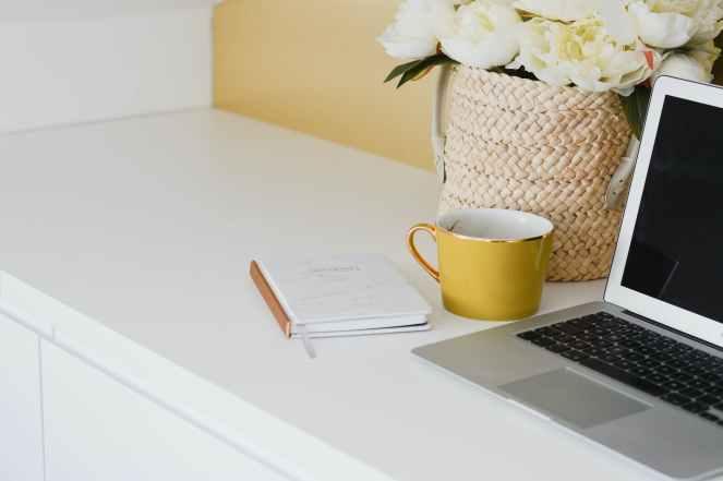 yellow mug besides laptop