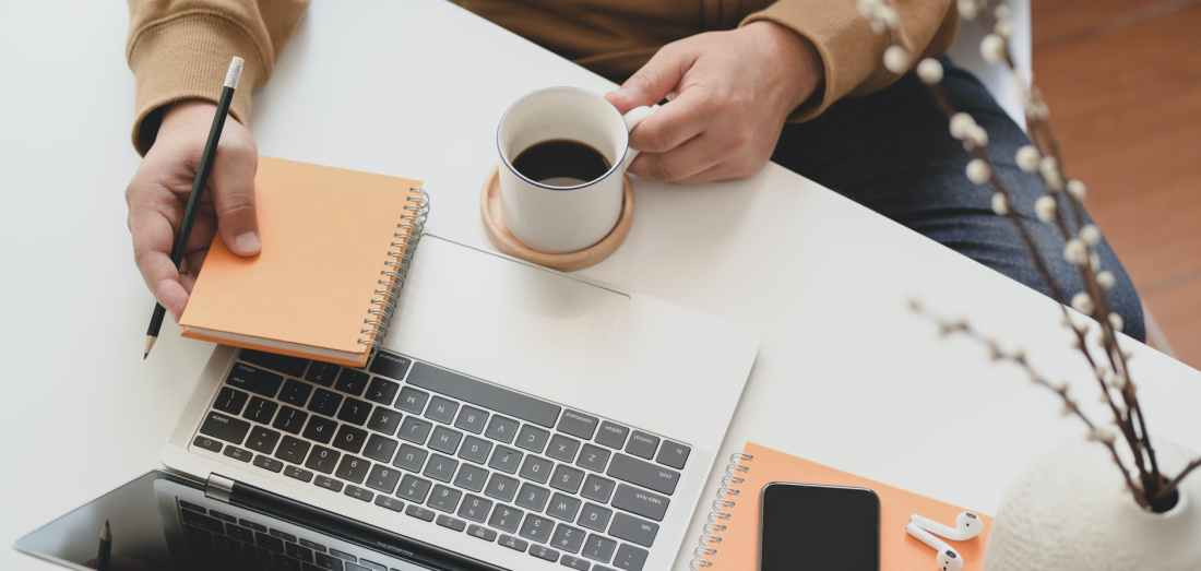 person holding white ceramic mug beside macbook pro