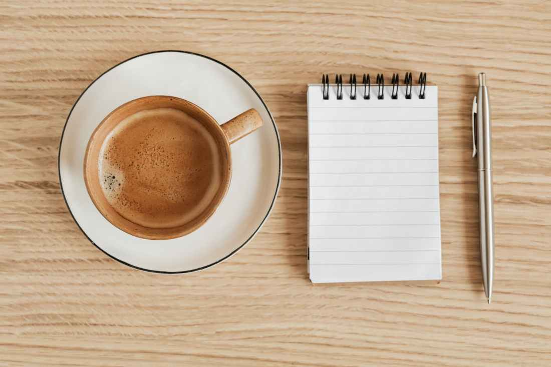 composition of coffee and notebook with pen